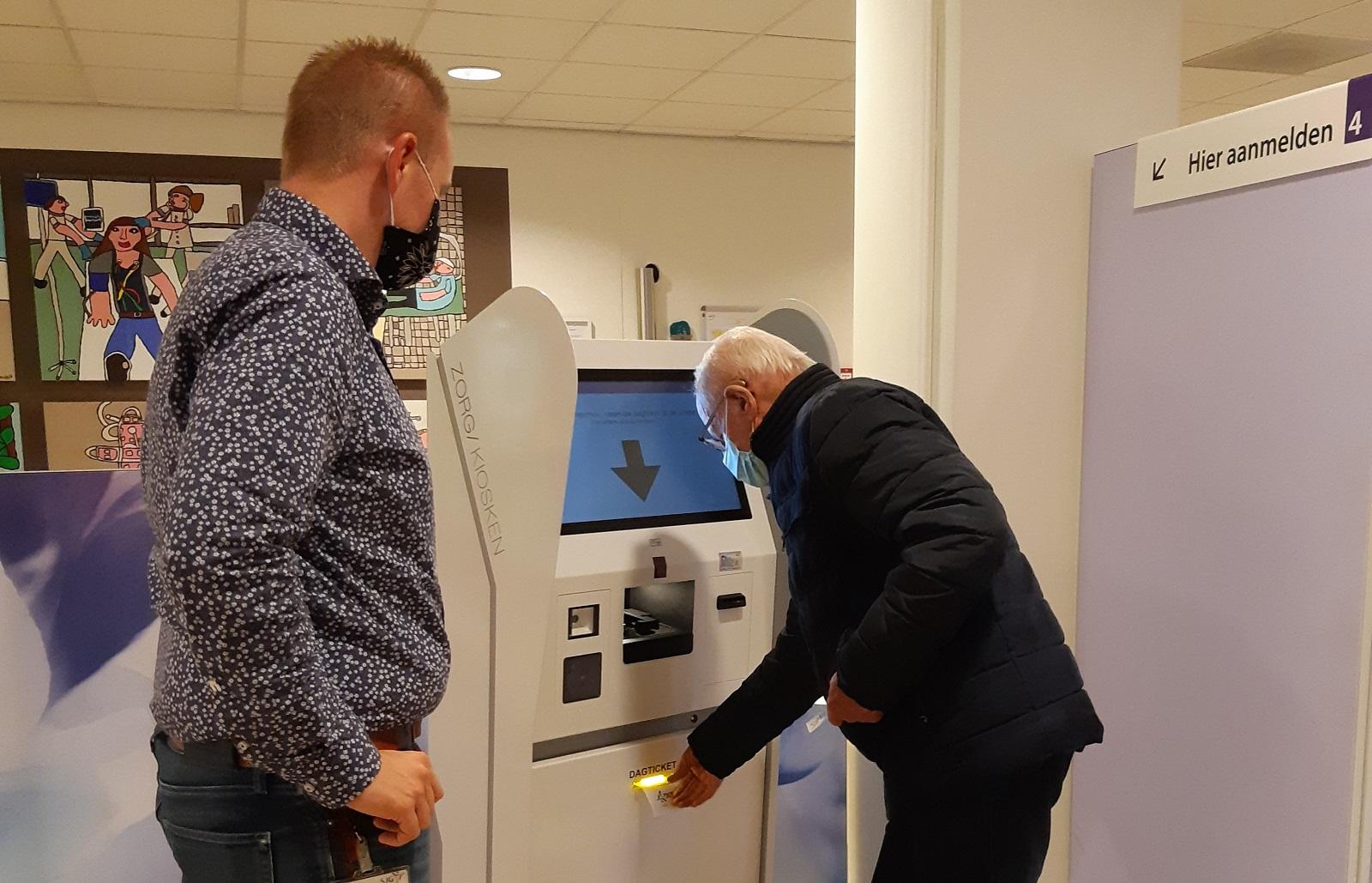 Roel Rinkens van SJG Weert helpt een patiënt bij de aanmeldzuil